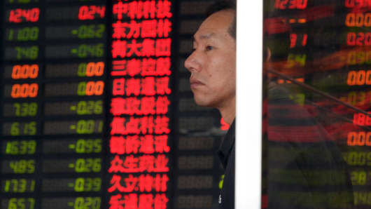 An investor in front of an electronic board showing stock information at a brokerage house in Shanghai, September 2, 2015.