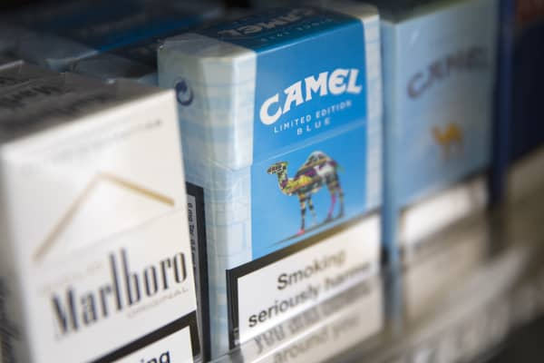A pack of Marlboro cigarettes, left, manufactured by Philip Morris International Inc., a unit of Altria Inc., sits beside packs of Camel cigarettes, manufactured by Reynolds American Inc.