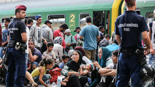 Police stand guard as migrants sit on the platform of Keleti station after it was reopened this morning in central Budapest on September 3, 2015.