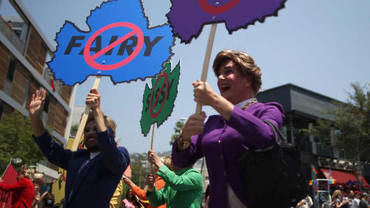 Men in drag hold banners at the LA Pride Parade in West Hollywood, California.