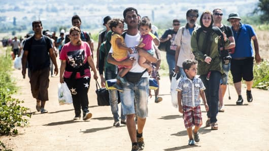A man carries two children as he walks with other migrants near the southern Serbian village of Miratovac, travelling on foot from Macedonia to Presevo in Serbia, on August 25, 2015. At least 2,000 more migrants flooded overnight into Serbia in a desperate journey to try and go on to Hungary, the door into the European Union, a UN official said on August 24. More than 9,000 people, mostly Syrian refugees, have arrived to Serbia those last three days.