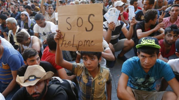 """A child holds a self-made placard reading """"SOS help me"""" outside the railways station in Budapest, Hungary September 2, 2015. Hundreds of migrants protest in front of Budapest's Keleti Railway Terminus for a second straight day on Wednesday, shouting """"Freedom, freedom!"""" and demanding to be let onto trains bound for Germany from a station that has been closed to them by Hungarian riot police officers."""