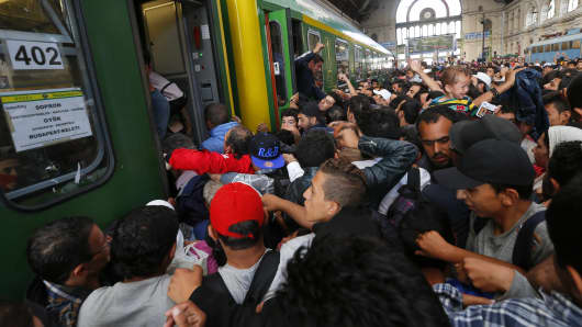 Migrants storm into a train at the Keleti station in Budapest, Hungary, September 3, 2015, after Hungarian police withdrew from the gates.