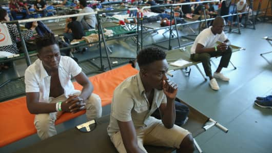 Migrants, including thee men from Benin, who had arrived by train to Germany sit on cots while waiting to register at a center for migrants at a facility of the German Federal Police (Bundespolizei) on August 31, 2015 in Rosenheim, Germany.