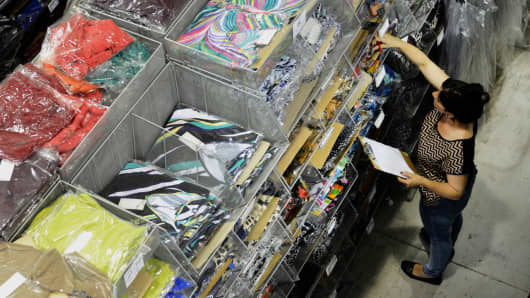 A worker at apparel distributor Beverly Rose searches through inventory to fill an order at the firm's warehouse in Miami.