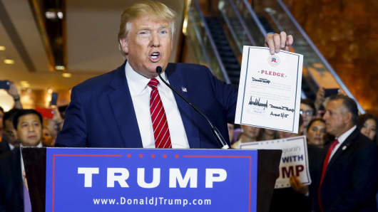 Donald Trump holds up a signed pledge at Trump Tower in New York September 3, 2015.