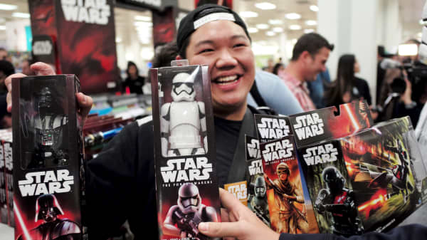 A shopper shows off his haul of new merchandise from the upcoming film 'Star Wars: The Force Awakens' at a department store open just after midnight on 'Force Friday' in Sydney, September 4, 2015.