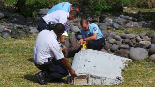 French gendarmes and police inspect a large piece of plane debris which was found on the beach in Saint-Andre, on the French Indian Ocean island of La Reunion, July 29, 2015. French prosecutor announced on Thursday that we can say with certainty that the wing part found on Saint-Andre beach was from missing Malaysia Airlines Flight MH370.