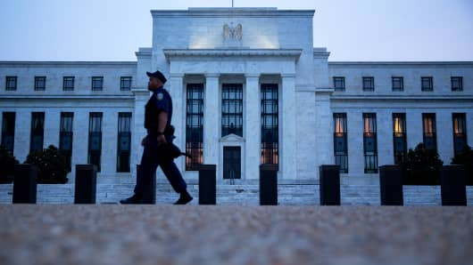 A Federal Reserve police officer walks past the Federal Reserve building in Washington, D.C.