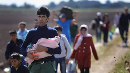 SZEGED, HUNGARY - SEPTEMBER 06: Hundreds of miigrants and refugees continue to cross the border from Serbia into Hungary along the railway tracks close to the village of Roszke on September 6, 2015 in Szeged, Hungary.