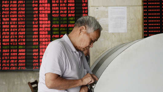 A stock investor monitors trading activity in a stock exchange in China.