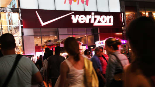 Pedestrians pass in front of a Verizon sign in New York City.