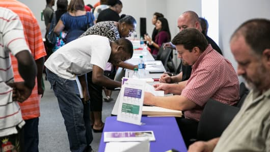 Job seekers fill out paperwork at booths during a weekly job fair event in Dallas, Sept. 2, 2015.