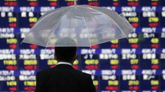 A pedestrian holding an umbrella looks at an electronic stock board outside a securities firm in Tokyo, Japan.