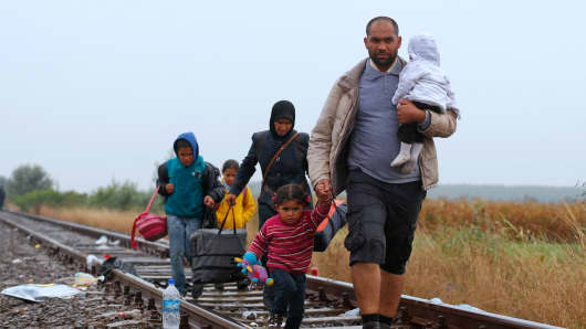 Migrants walk along a rail track in the rain from Roszke to Szeged in Hungary, September 10, 2015.