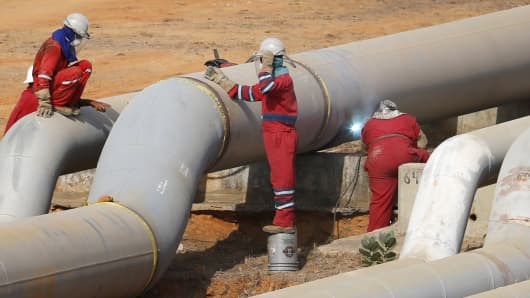 Oil workers weld a new pipeline at PDVSA's Jose Antonio Anzoategui industrial complex in the state of Anzoategui, Venezuela.