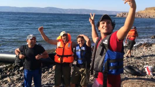 Refugees take a selfie after safely arriving on the Greek island of Lesbos with Turkey behind them.