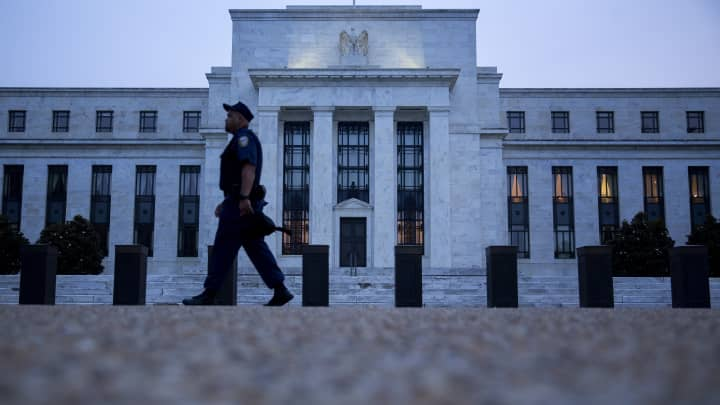 A Federal Reserve police officer walks past the Marriner S. Eccles Federal Reserve building in Washington, D.C.