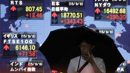 A pedestrian holding an umbrella stands in front of an electronic stock board displaying the Nikkei 225 Stock Average outside a securities firm in Tokyo, Japan.