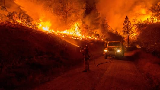 A firefighter douses flames from a backfire while battling the Butte fire near San Andreas, California on September 12, 2015. Wildfires have spread rapidly through northern California, destroying hundreds of homes, forcing thousands of people to flee and injuring four firefighters.