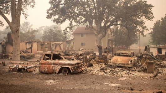 Burned out vehicles are surrounded by smoldering rubble while firefighters continue to battle the Valley fire in Middletown, California on September 13, 2015. The governor of California declared a state of emergency Sunday as raging wildfires spread in the northern part of the drought-ridden US state, forcing thousands to flee the flames.