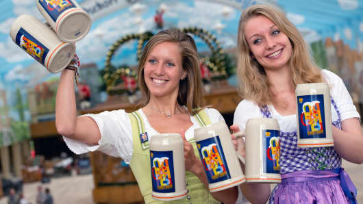 Women wearing the traditional Bavarian Dirndls present the offical Oktoberfest beer mugs at the Oktoberfest grounds in Munich, southern Germany, on August 18, 2015.