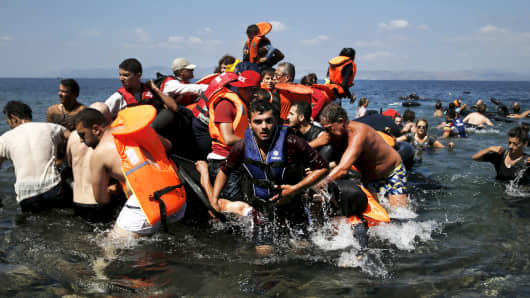 Syrian and Afghan refugees are helped by locals and volunteers as they reach the shore after their dinghy deflated some 100m away from the Greek island of Lesbos, September 13, 2015.