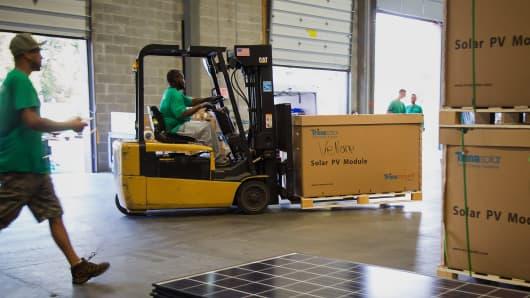 A forklift operator moves a pallet of solar panels at the SolarCity warehouse facility in Cranbury, New Jersey.
