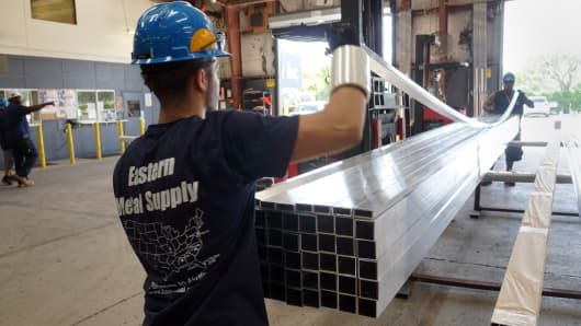 Workers prepare an order of aluminum materials for shipping at the Eastern Metal Supply facility in Lake Worth, Florida.