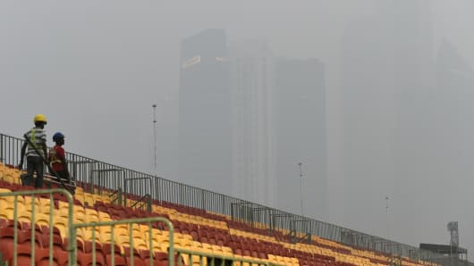 Workers install spectators seats for the Formula One street circuit as financial district buildings are shrouded with haze in Singapore on September 14, 2015.