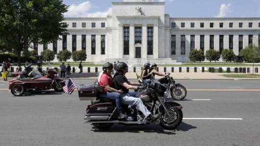 Motorcyclist ride by the Federal Reserve Building in Washington, DC.