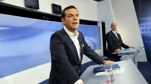 Former Greece's prime minister and leftist Syriza party leader Alexis Tsipras (L) and New Democracy party leader Vangelis Meimarakis stand at their podiums before a televised debate in Athens, September 14, 2015.
