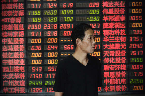 An investor looks on at a stock exchange hall in Shanghai, China.