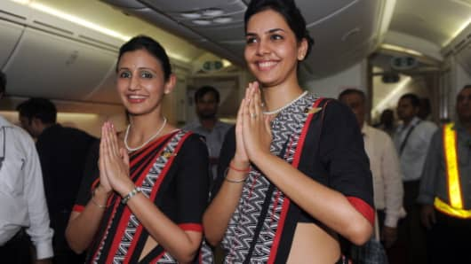 Air India flight attendants pose for a photo during the unveiling of Air India's first Boeing 787 Dreamliner at Indira Gandhi International airport terminal 3 in New Delhi.