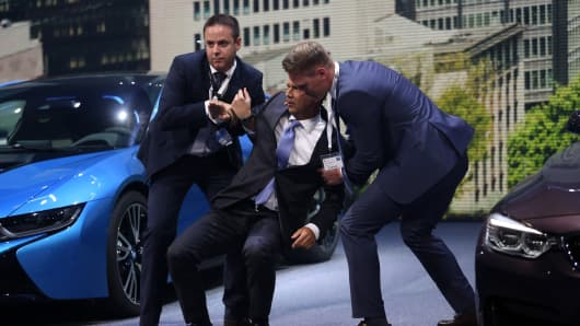 Harald Krueger, chief executive officer of Bayerische Motoren Werke AG (BMW), center, is assisted after collapsing during a BMW press conference at the IAA Frankfurt Motor Show in Frankfurt, Germany, on Tuesday, Sept. 15, 2015.