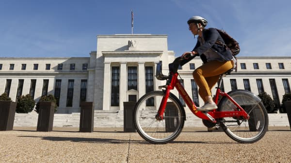 A cyclist passes the Federal Reserve headquarters in Washington.