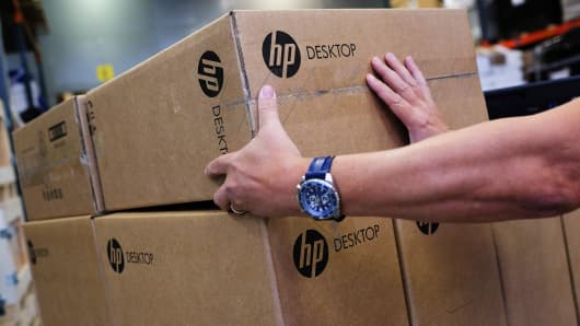 An employee selects a packaged HP desktop computer from a pallet in a London warehouse.