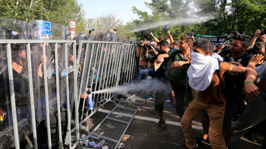 Hungarian police use pepper spray against migrants at the Horgos border on September 16, 2015.