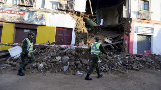 Police officers put barricade tape in front of a damaged building after an earthquake hit areas of central Chile, in Illapel town, north of Santiago, Chile, September 17, 2015.