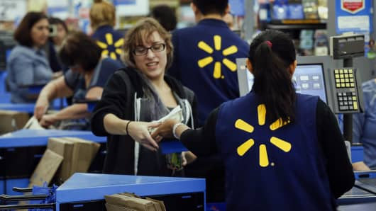 Employees assist shoppers at the check out counter of a Walmart store in Los Angeles.