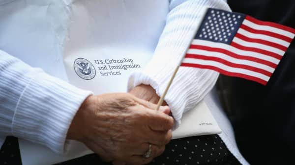 Immigrants from 25 countries participate in a naturalization ceremony.