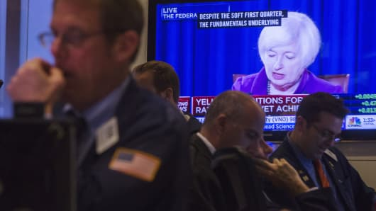 Traders work on the floor of the New York Stock Exchange, as a television screen displays Federal Reserve Chair Janet Yellen speaking on June 17, 2015.