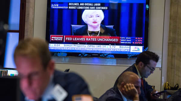 A trader works on the floor of the New York Stock Exchange while Federal Reserve Chairwoman Janet Yellen explains why the Federal Reserve chose not raise interest rates on September 17, 2015 in New York