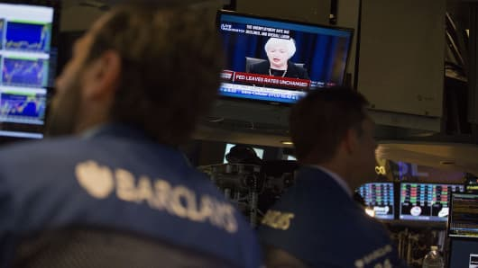 Traders work as Janet Yellen, chair of the U.S. Federal Reserve, is seen speaking on a television screen on the floor of the New York Stock Exchange (NYSE) in New York, U.S., on Thursday, Sept. 17, 2015.
