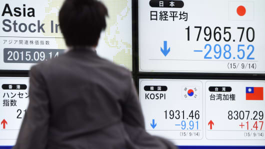 A businessman runs past an electric quotation board flashing the Nikkei key index in Tokyo, Japan.