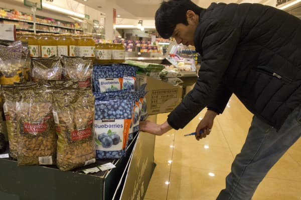 A worker handles bags of almonds packaged as originating from California at a supermarket in Beijing. About 60 to 70 percent of California almonds are sold internationally.