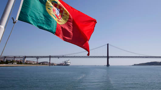Portuguese Flag waves in sight of the 25 de Abril Bridge in Lisbon, Portugal.