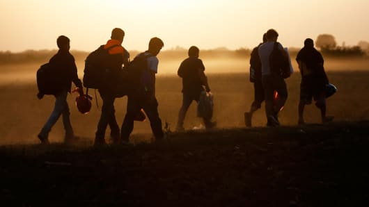 Migrants walk on a dirt road as they approach the Croatian border near the town of Sid, Serbia, September 18, 2015.