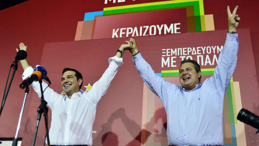 Syriza leader Alexis Tsipras (L) celebrates with Independent Greeks (ANEL) party leader Panos Kamenos after his party's victory in the Greek general elections at his campaign headquarters in Athens on September 20, 2015.