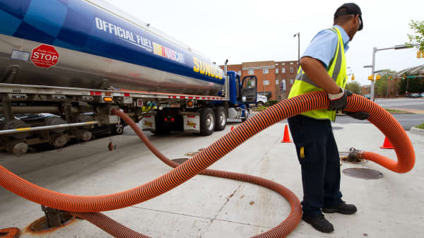 A tanker truck driver unloads various grades of gasoline into the underground tanks at a Sunoco gas station in Arlington, Virginia.